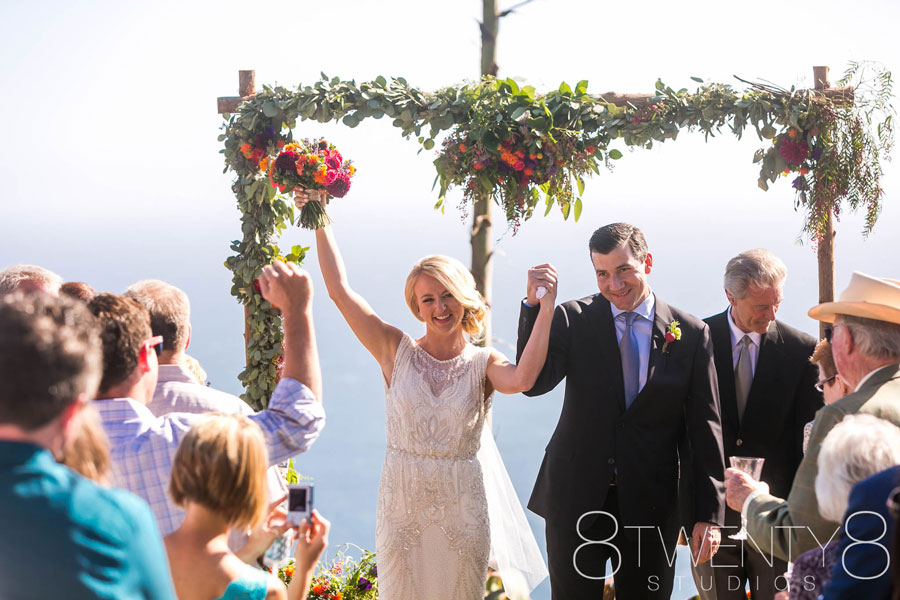 Happy Bride and Groom with a Bouquet and Wedding Arch by Kate Healey