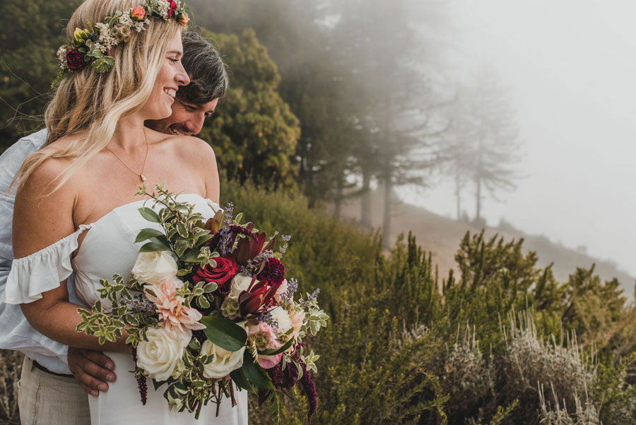 Couple Embraced on Their Wedding Day with Flowers by Kate Healey