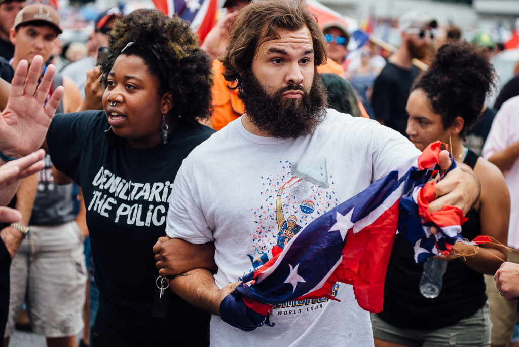 Elle Lucier and Tommy DiMassimo lock arms as they move through the crowd at the Confederate flag rally.