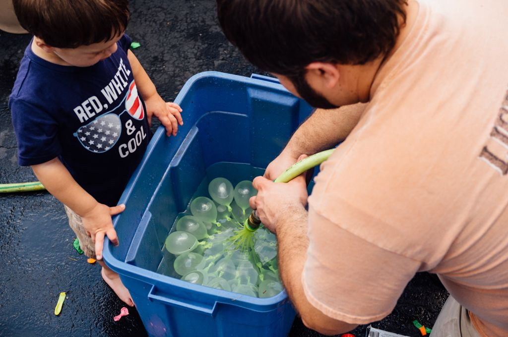 Dennis, right, fills a bin with water balloons for his son Nolan.