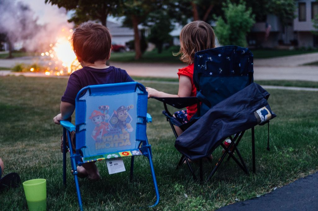 Nolan and Chase watch their neighbors set off fireworks in the front yard.