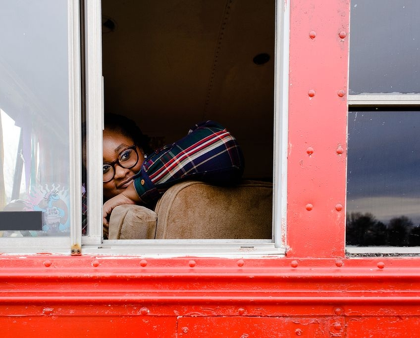 Candra looks out the school bus's driver side window.