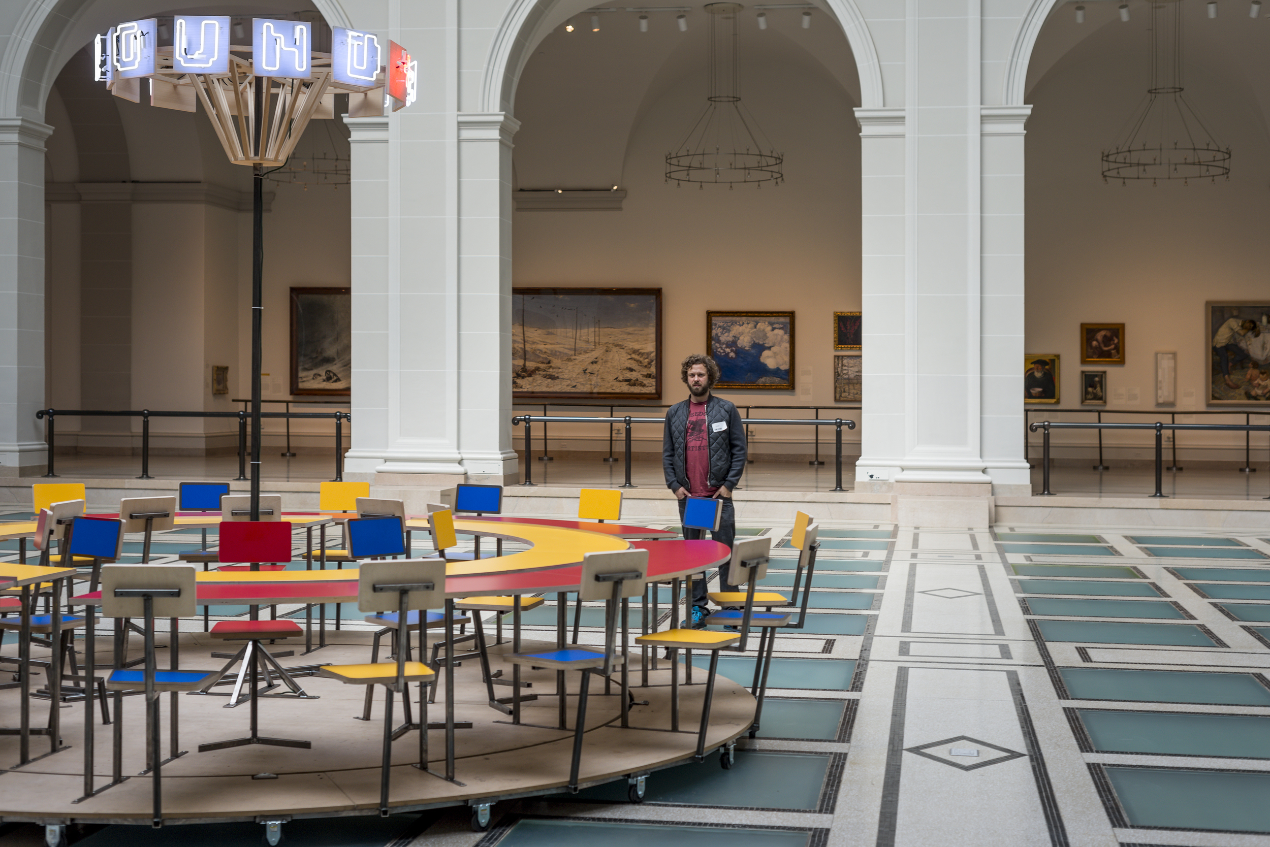 Oliver Clegg pictured with  Until the Cows Come Home  (2014), as installed at the Brooklyn Museum in 2014. Steel, neon, laminated mdf, pine; 60 x 168 in. (table), 24 x 60 in. (neon centerpiece). ( photo : Giles Ashford)
