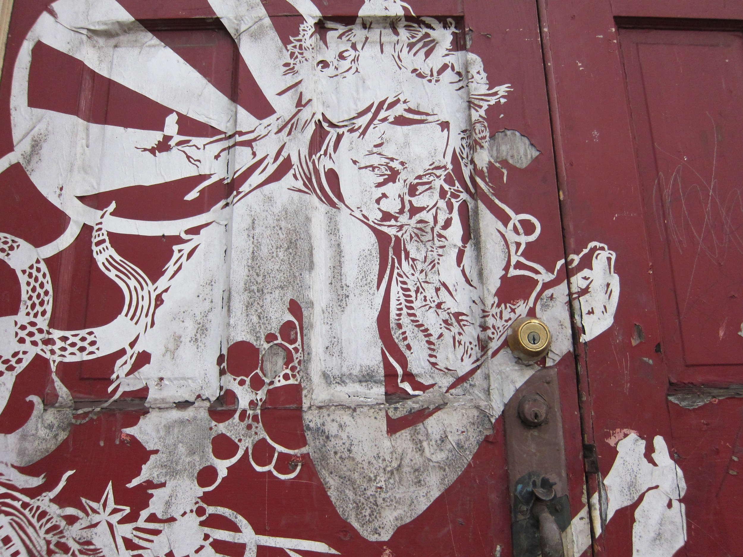 A 2010 pasted work adorning the door of a formerly abandoned church in Braddock, Pennsylvania – now home to the Braddock Tiles community arts initiative. ( Photo : Tod Seelie)