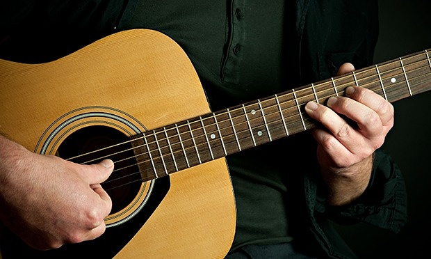 Traditional Guitar Playing Example ( source ) Notice the under-neck playing position and vertical frets.