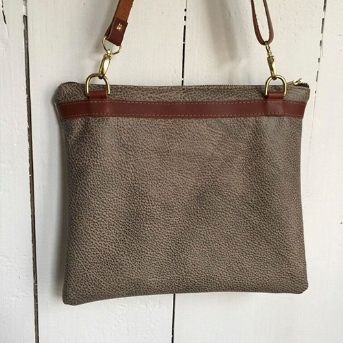 The leather on the back of each bag is unique and coordinates with the image on the front. Brass hardware completes the look of the bags.