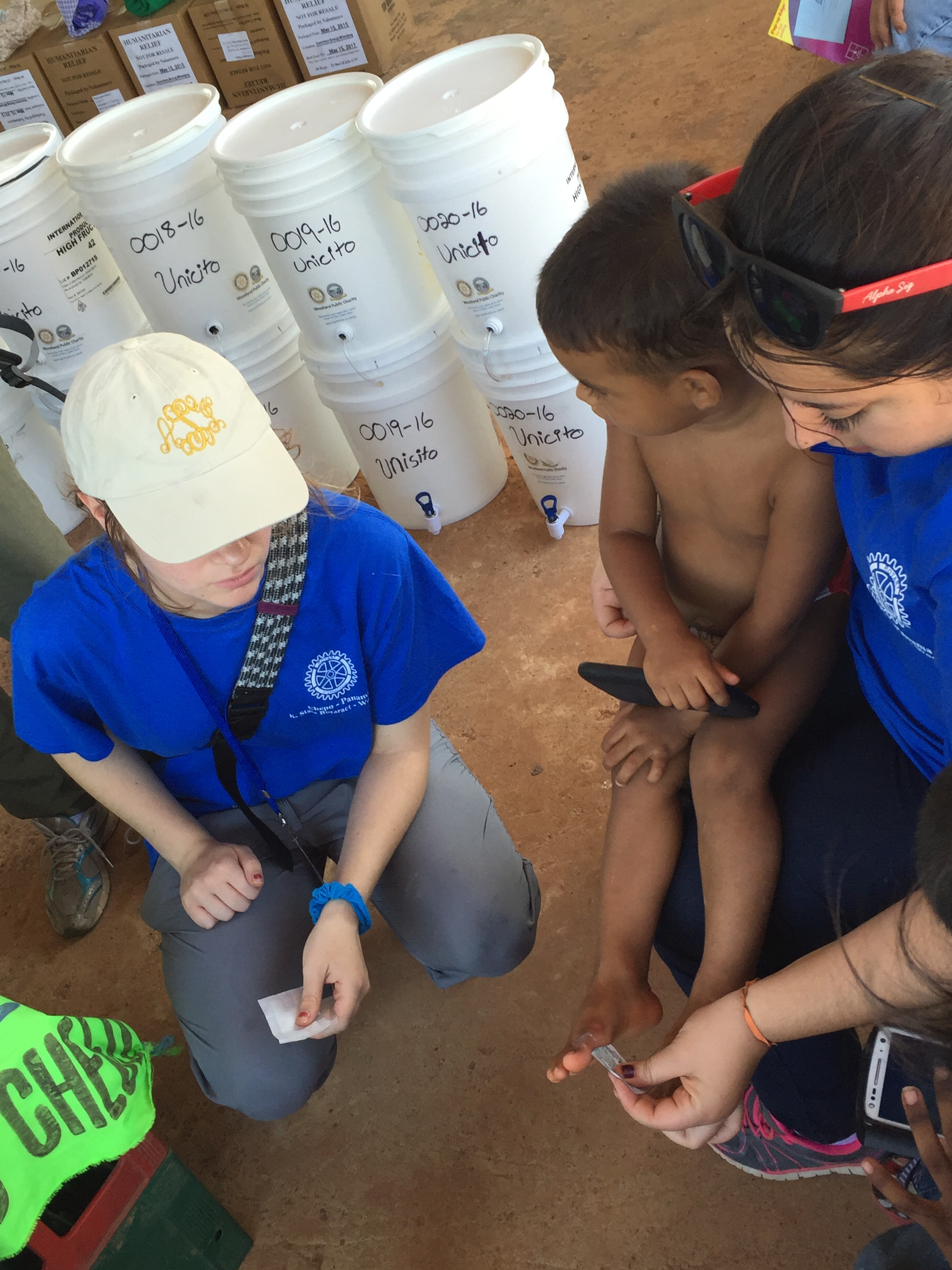 Amanda and Karina (of WPC) clean and bandage a cut on the toe of a young boy walking around without shoes.