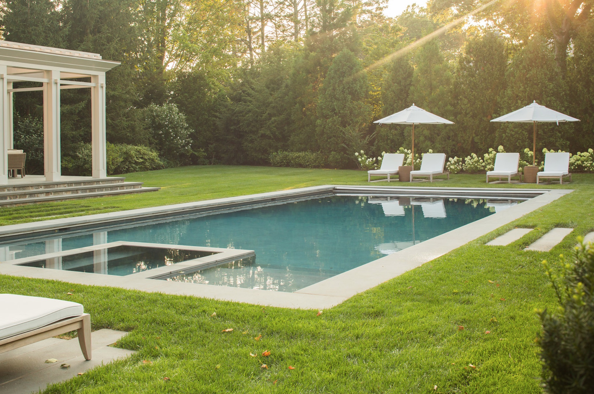 Swimming pool set in lawn with paving islands for easy lounging.  Tall evergreen screening trees.