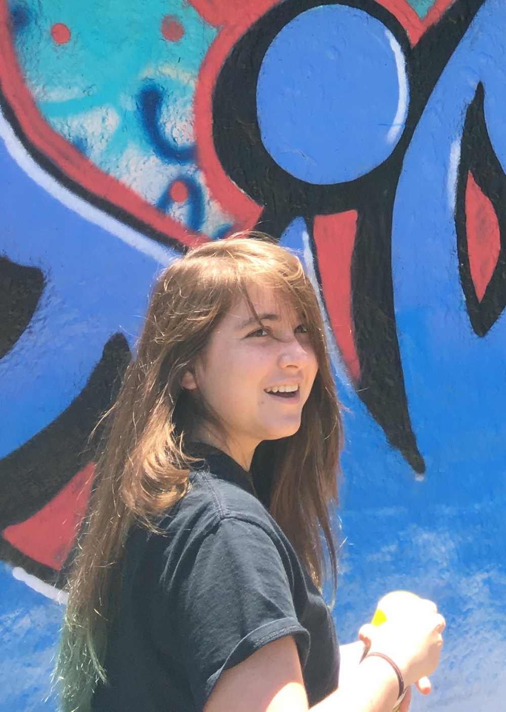 Image Description: A young woman (Genevieve Wilhelm) with long brown hair with teal dyed tips stands in front of a blue and red graffiti wall, turning and laughing at something.