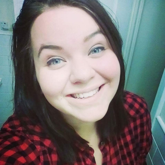 Image Description: A young brunette woman with blue eyes is smiling in a selfie, she is wearing a red plaid flannel and is posed against a green tile wall.