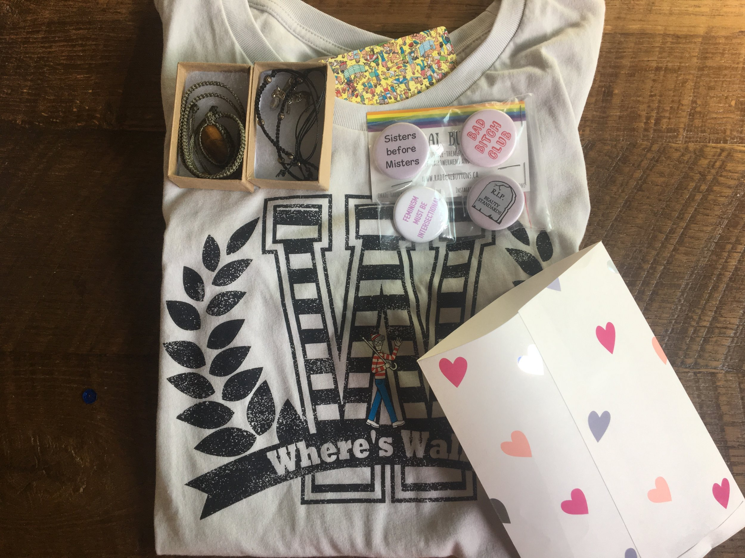 """Image Description: Items in give away pictured here. One grey """"Where's Wally?"""" t-shirt, two bracelets, one gift bag with hearts on it, and four pins with various feminist statements."""
