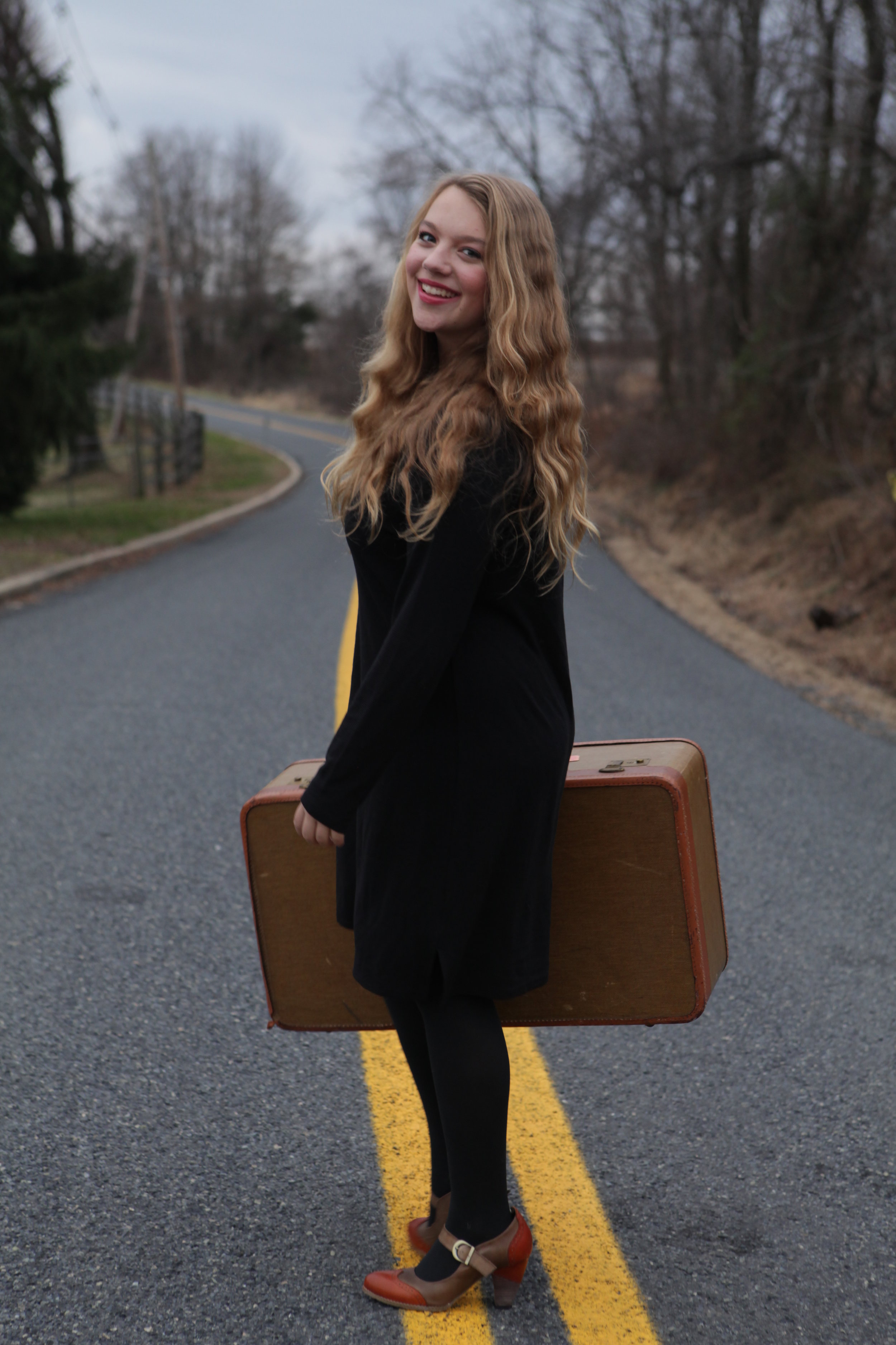 Image Description: A young woman, Grace, with long blonde hair stands smiling in the middle of a road with forrest on either side holding a suitcase.