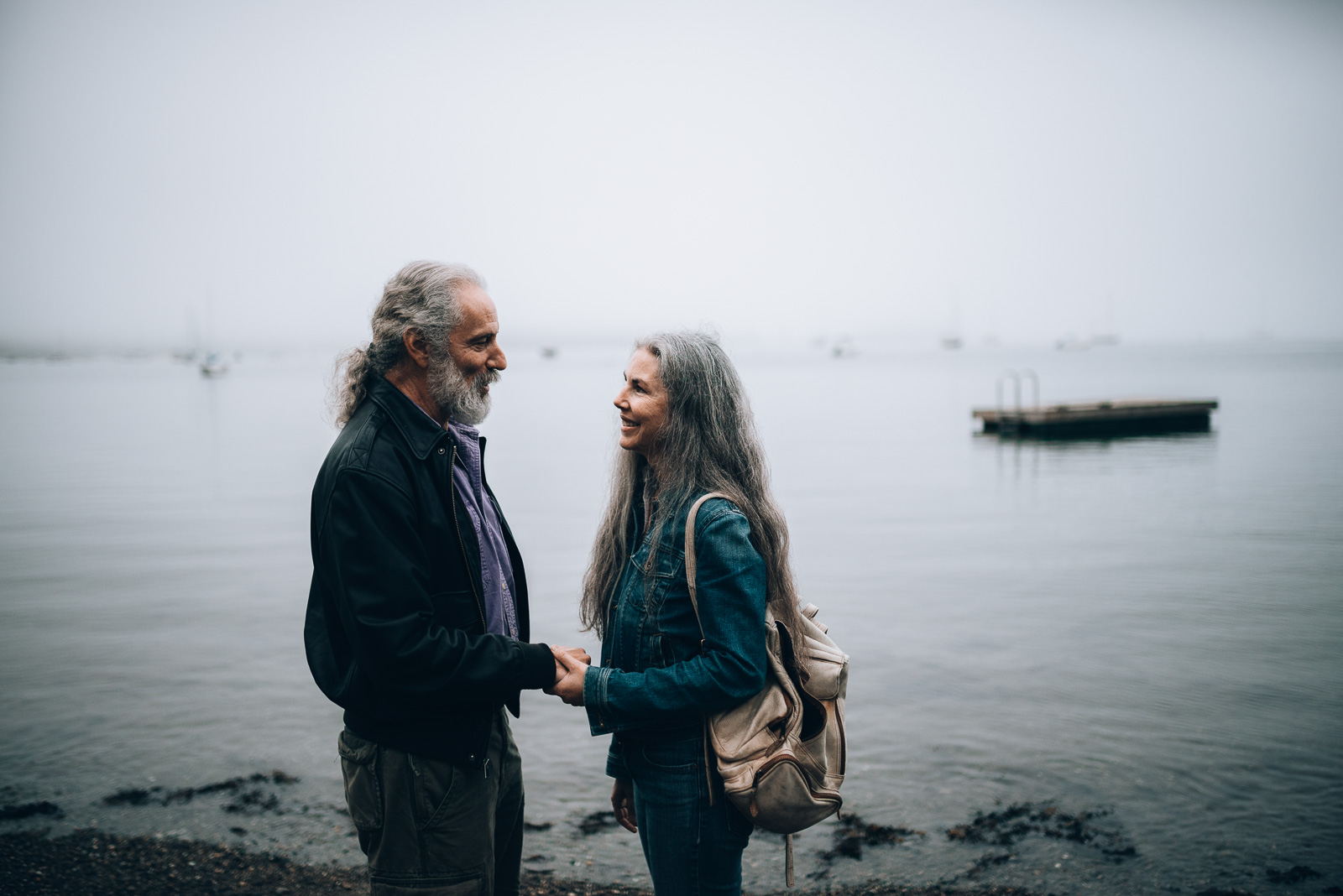 a married couple holding hands and looking into each other's eyes at Laite Beach in Camden, Maine on their 30th wedding anniversary
