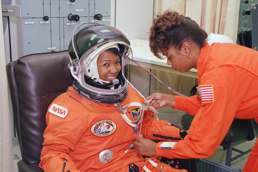 NASA_astronaut_Mae_Jemison_waits_as_her_suit_technician,_Sharon_McDougle,_performs_a_unpressurized_and_pressurized_leak_check_on_her_spacesuit.jpg