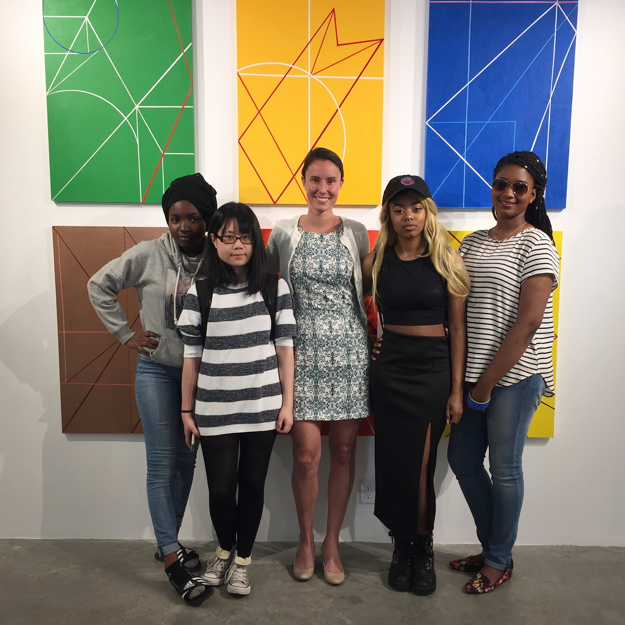 Our gallery director, Abigail Ogilvy, and AFH teens in front of their artwork