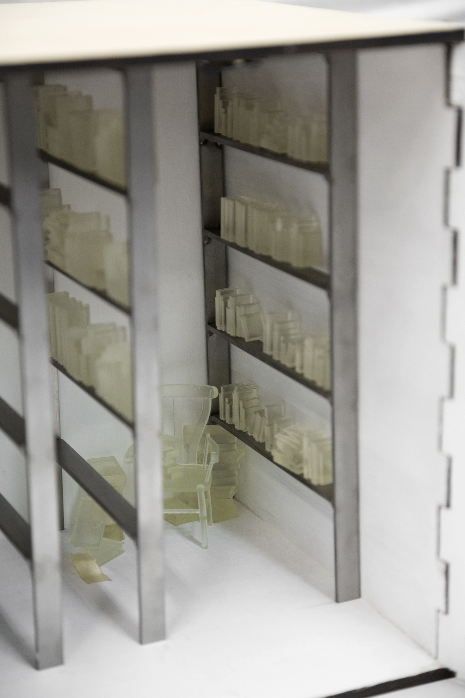 Kristina McComb, Close up detail of 3D printed books scattered across the miniature library shelves