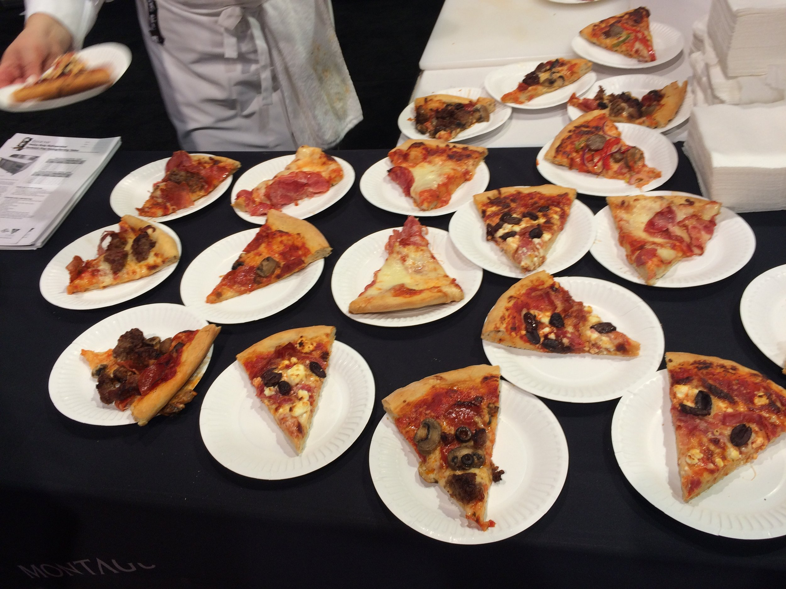 Slices of pizza out in the wild of Pizza Expo