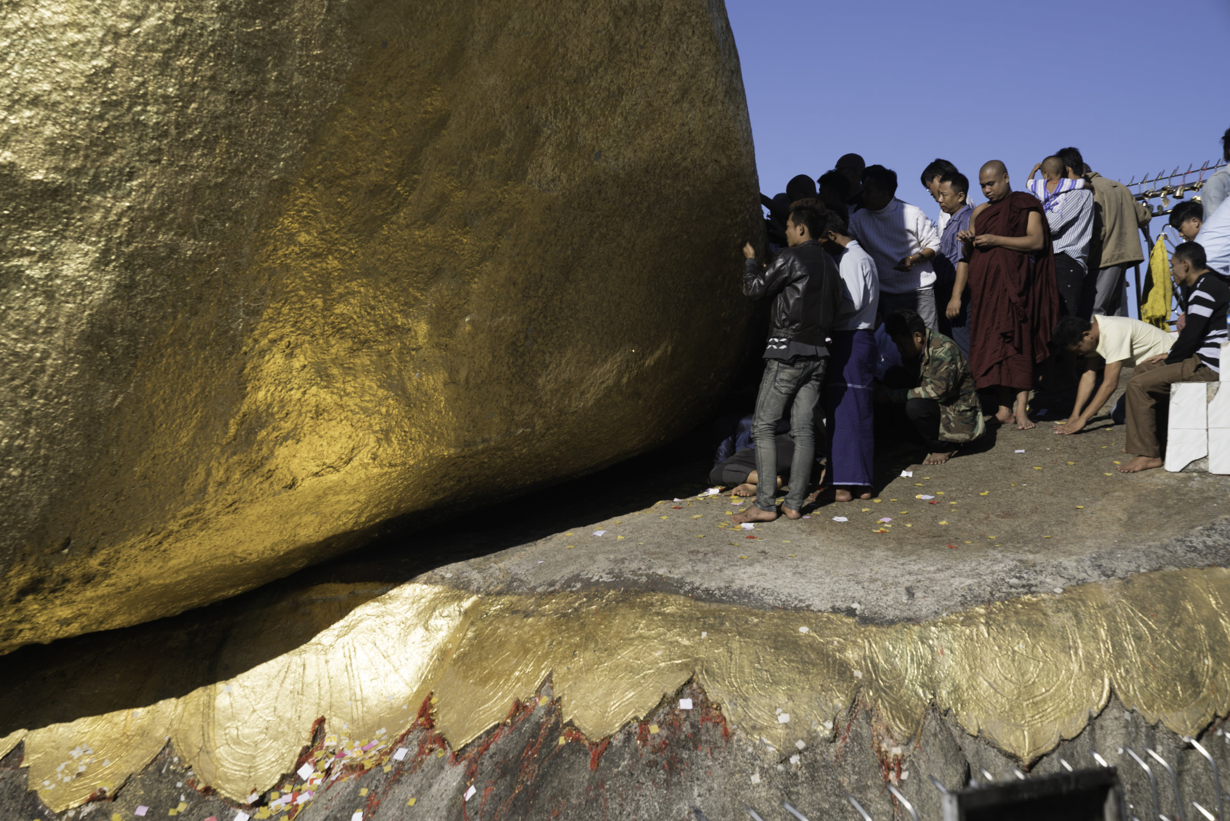 Pilgrims and devotees pasting pure gold leaves on the side of the golden rock.