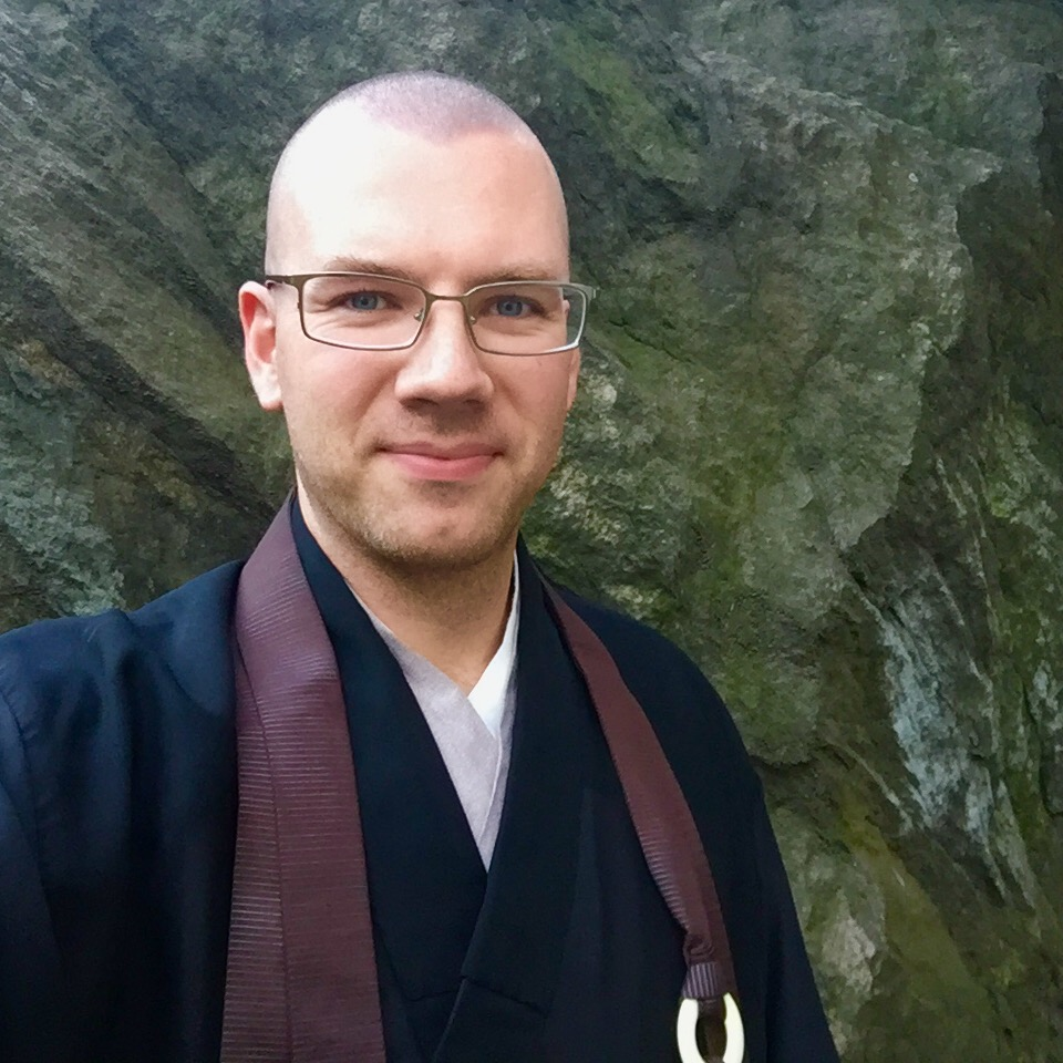 Oshin smiling, wearing a brown rakusu, standing in front of a large rock.