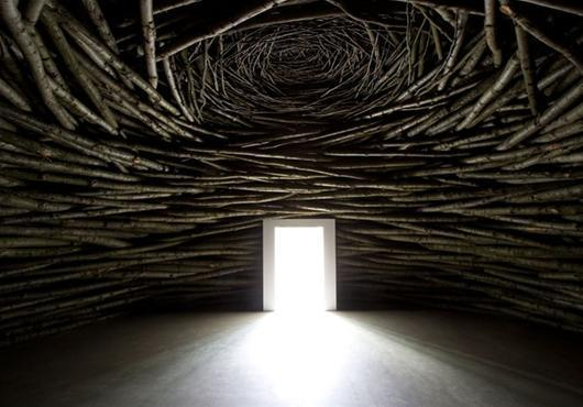 Image Description: A sculptural room by Andy Goldsworthy, an interior shot of a room made of sticks with a doorway streaming in light.