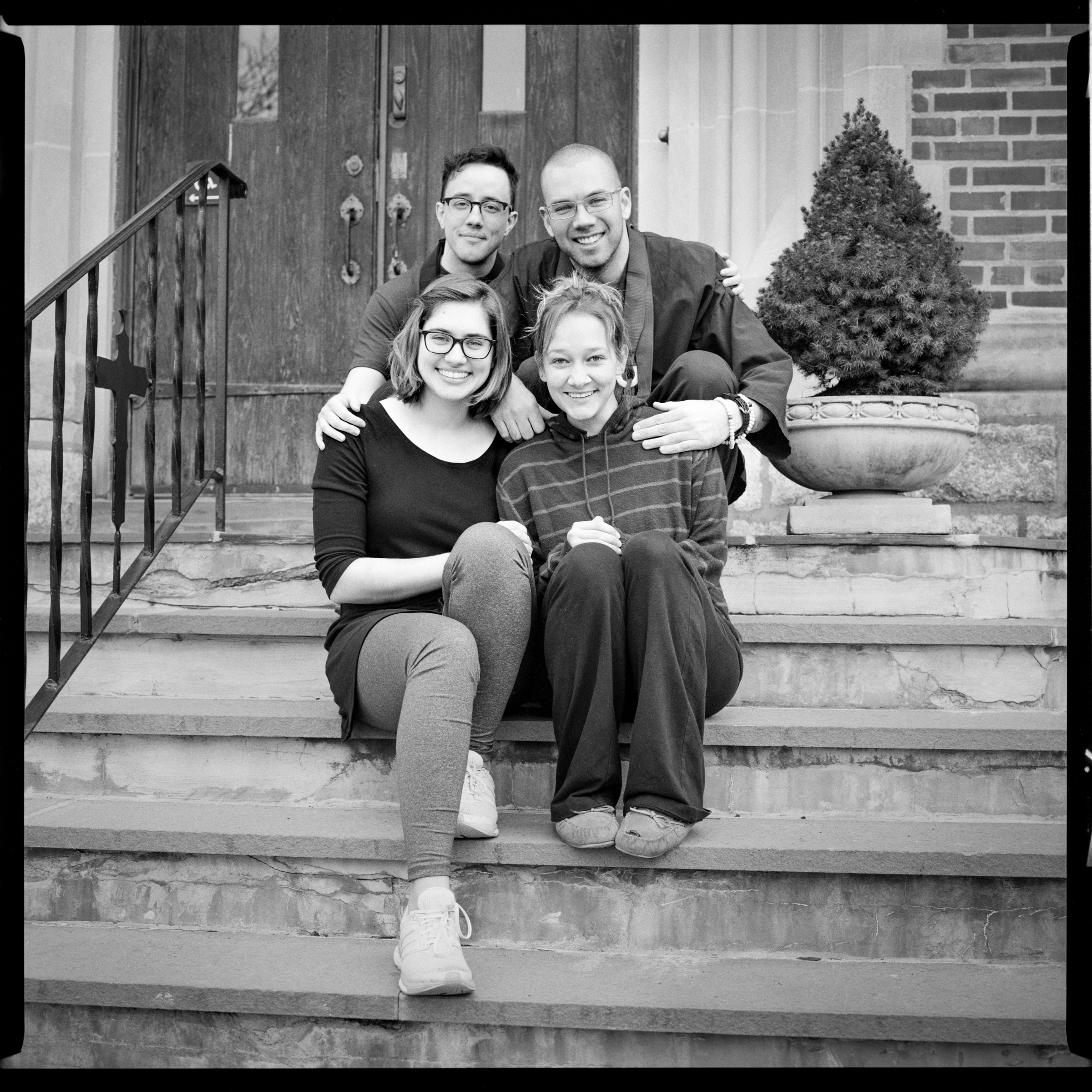 Image description: black and white photo of Giyu, Oshin, Mandy, and Erica sitting huddled together on stone steps in front of an old building. They are smiling and their hands are draped on each other.