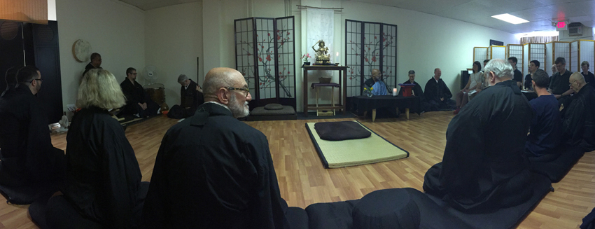 An interior shot of Soji Zen Center, a panorama showing many meditators wearing black robes and the altar.