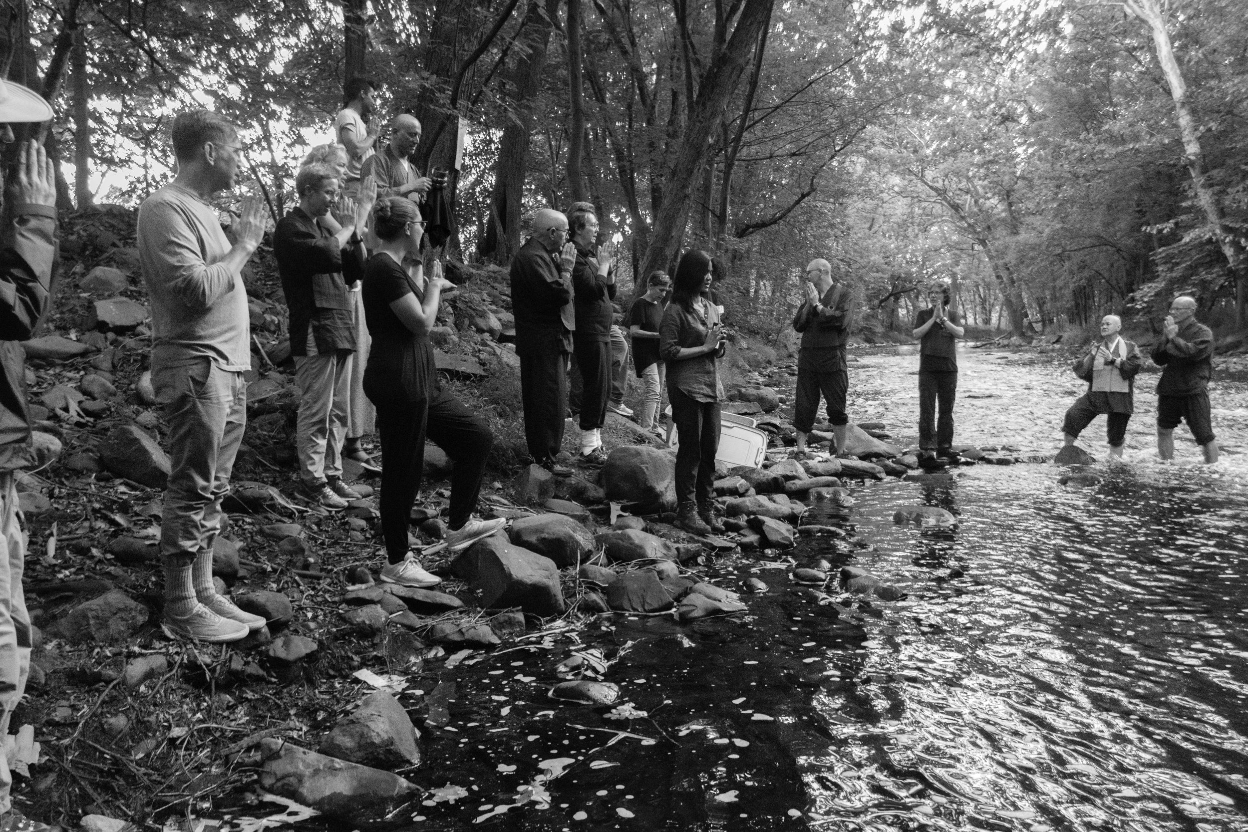 Members of Village Zendo stand along a river bank during the Obon ceremony honoring people who passed away.