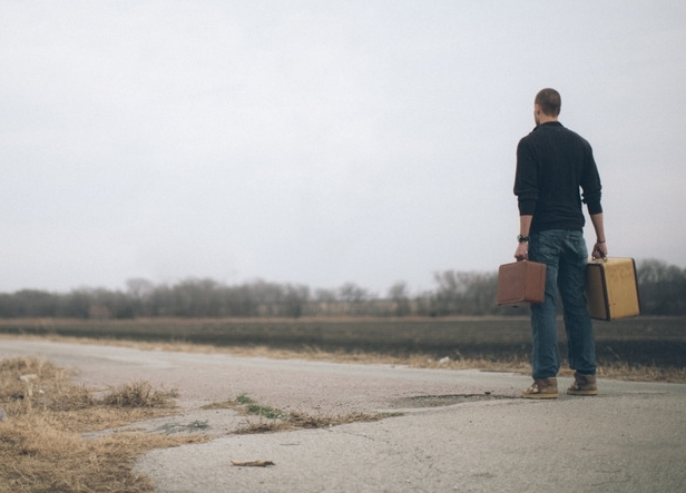 lightstock-60120-man-walking-down-the-middle-of-a-road-carrying-suitcases--2 copy.jpg