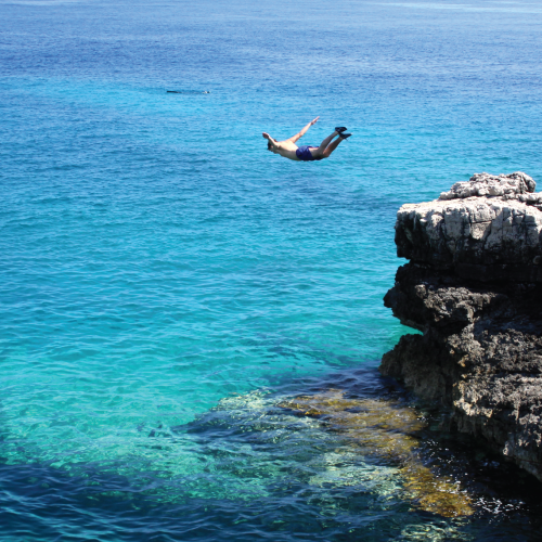 A man dives off of a cliff into the beautiful, clear water below.