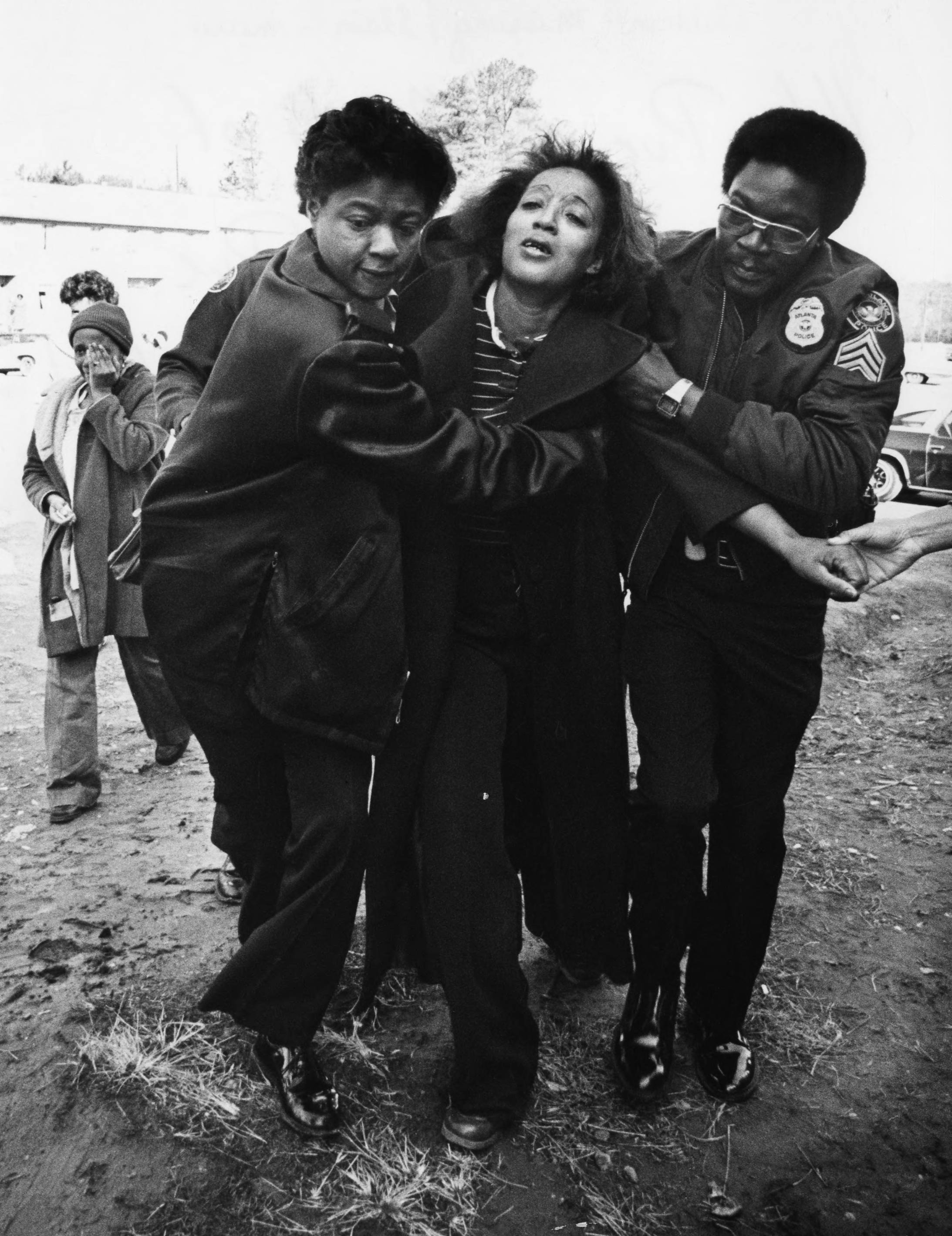 Helen Pue, mother of murdered Terry Pue helped into her apartment by police.  Photograph by George Clark (1981) Atlanta Journal-Constitution Photographic Archives. Special Collections and Archives, Georgia State University Library.