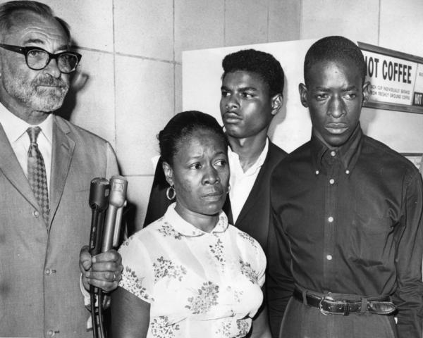 Attorney A. L. Wirin, left, with Mrs. Rena Frye, accused of interfering with officers who arrested her sons, Ronald, center, and Marquette, right. Photograph via L.A. Times (1965)