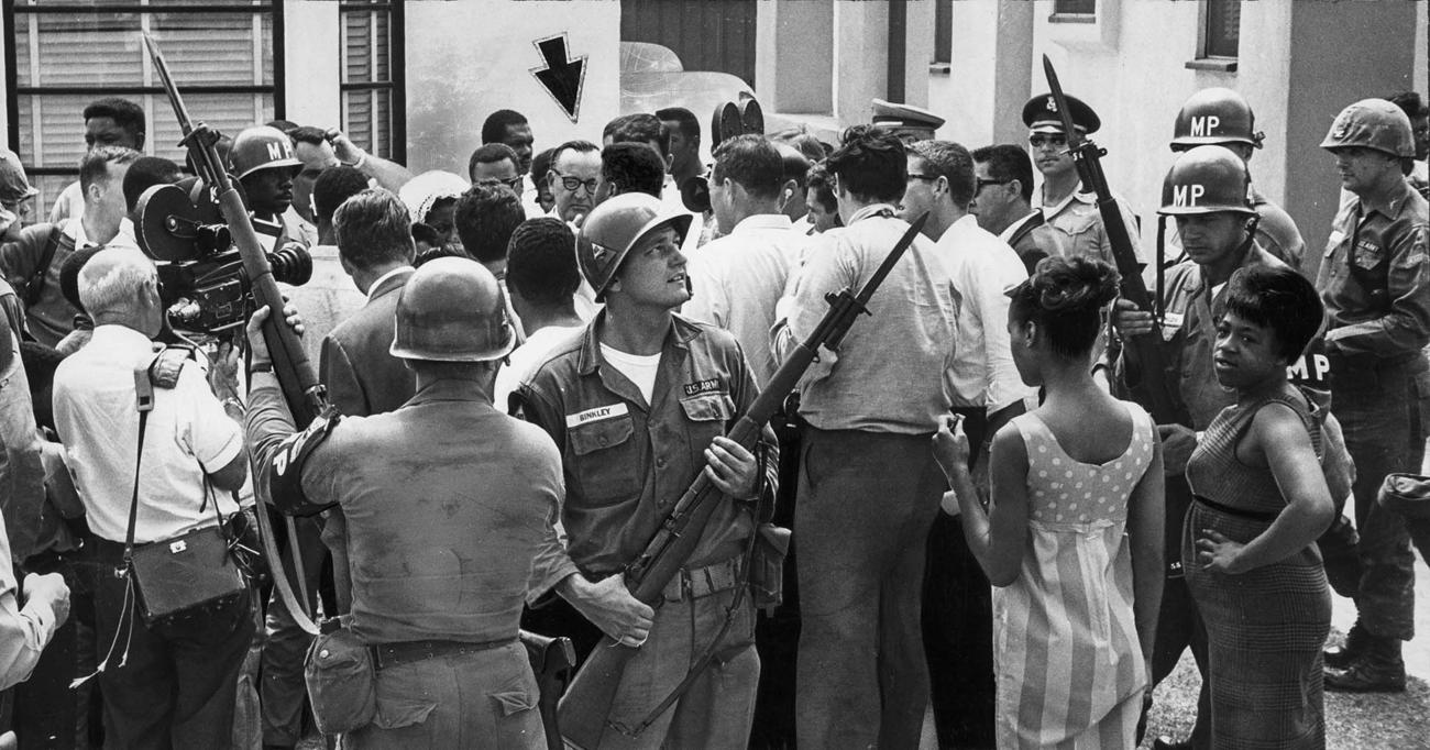 Local residents and journalists converge on California Gov.Pat Brown, under arrow, as he arrives at Jacob Riis High School to have lunch with high-ranking National Guard officers. (Bill Murphy / Los Angeles Times) 1965