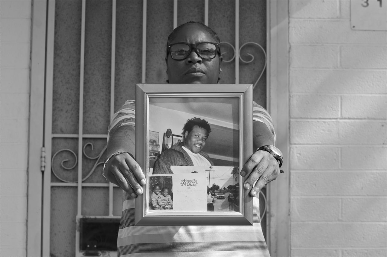 Sherika Simms holds the last photo taken of her brother, Maurio Proctor, outside one of their childhood apartments in Jordan Downs.  Sahra Sulaiman/LA Streetsblog