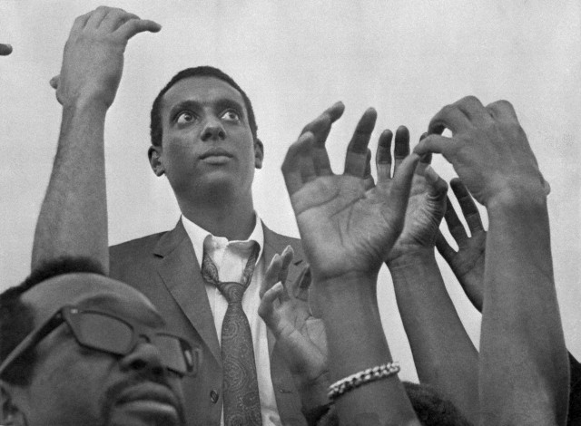 """""""Black Power"""" advocate Stokely Carmichael was repeatedly cheered as he addressed a crowd of about 2,500 persons at a rally in Will Rogers Park in Watts. He spoke from a flatbed of a truck and urged Watts citizens to form their own city, their own police force and their own schools. 1966 Bettmann/CORBIS"""