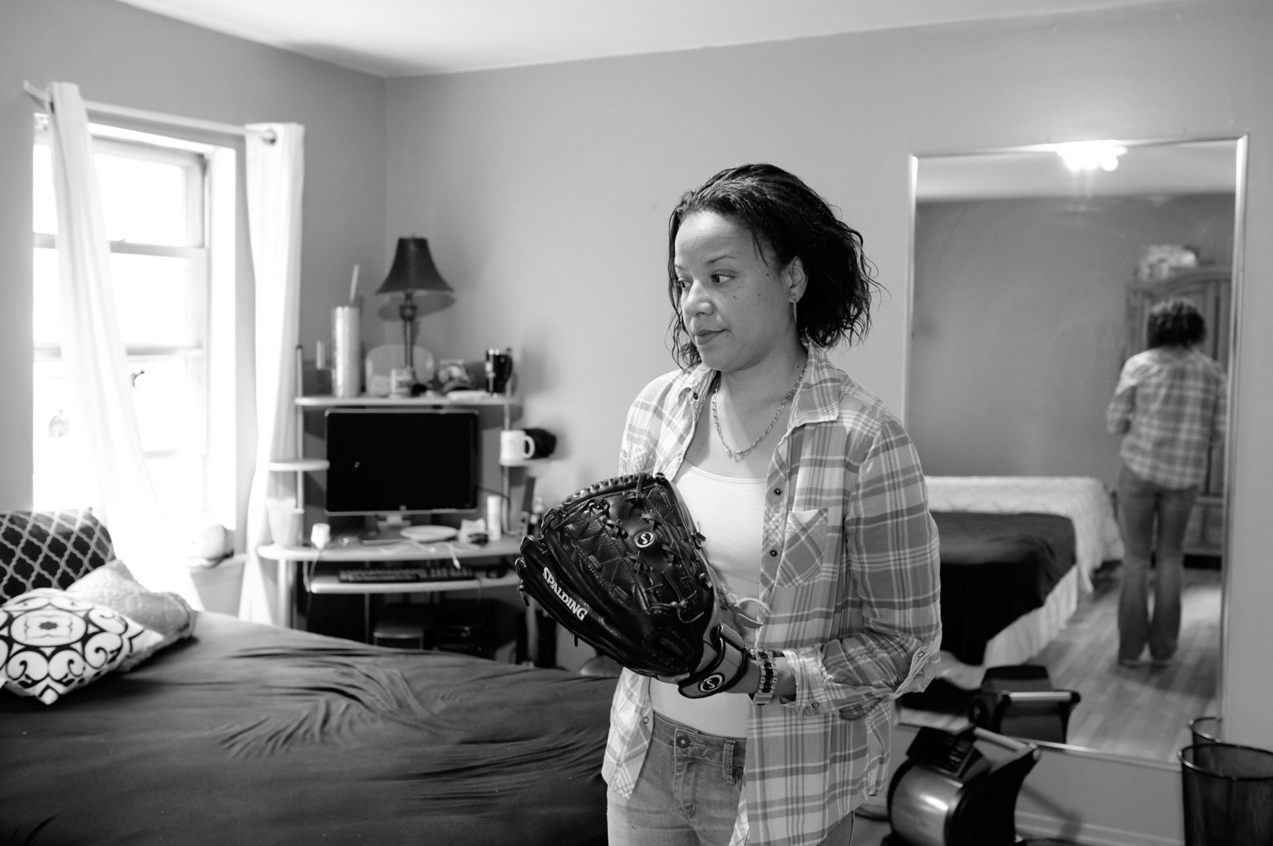 "Keila living in her cousin's home after her release from prison. Long Island, New York (2014)   ""My dad bought me this softball glove when I joined the prison team. He died while I was in there. Two officers transported me to the funeral home. I was in cuffs for twenty hours. He was the man I loved the most in this whole world. It just went all wrong. They made it worse."""