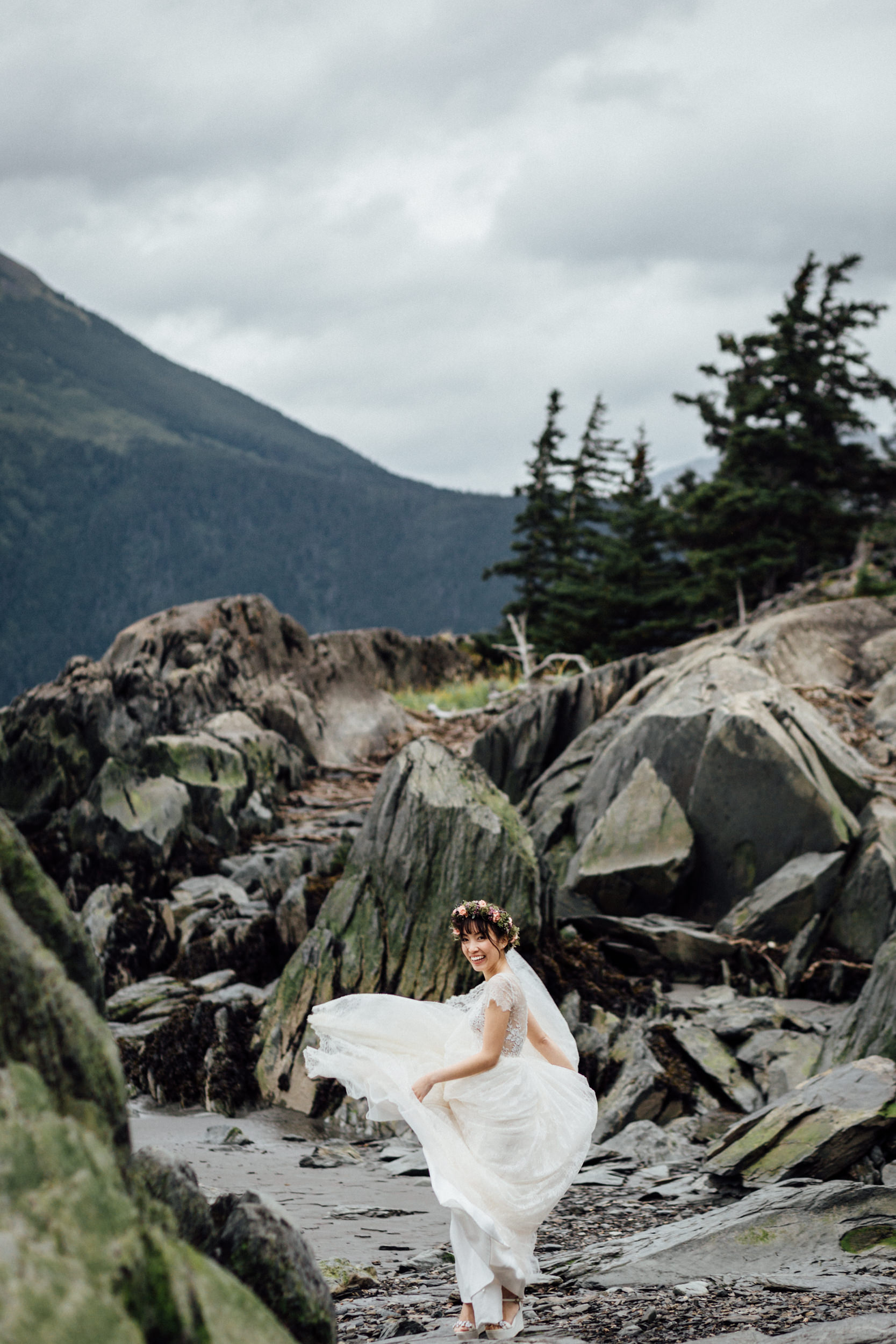 Bride twirling dress on rocky Alaskan beach