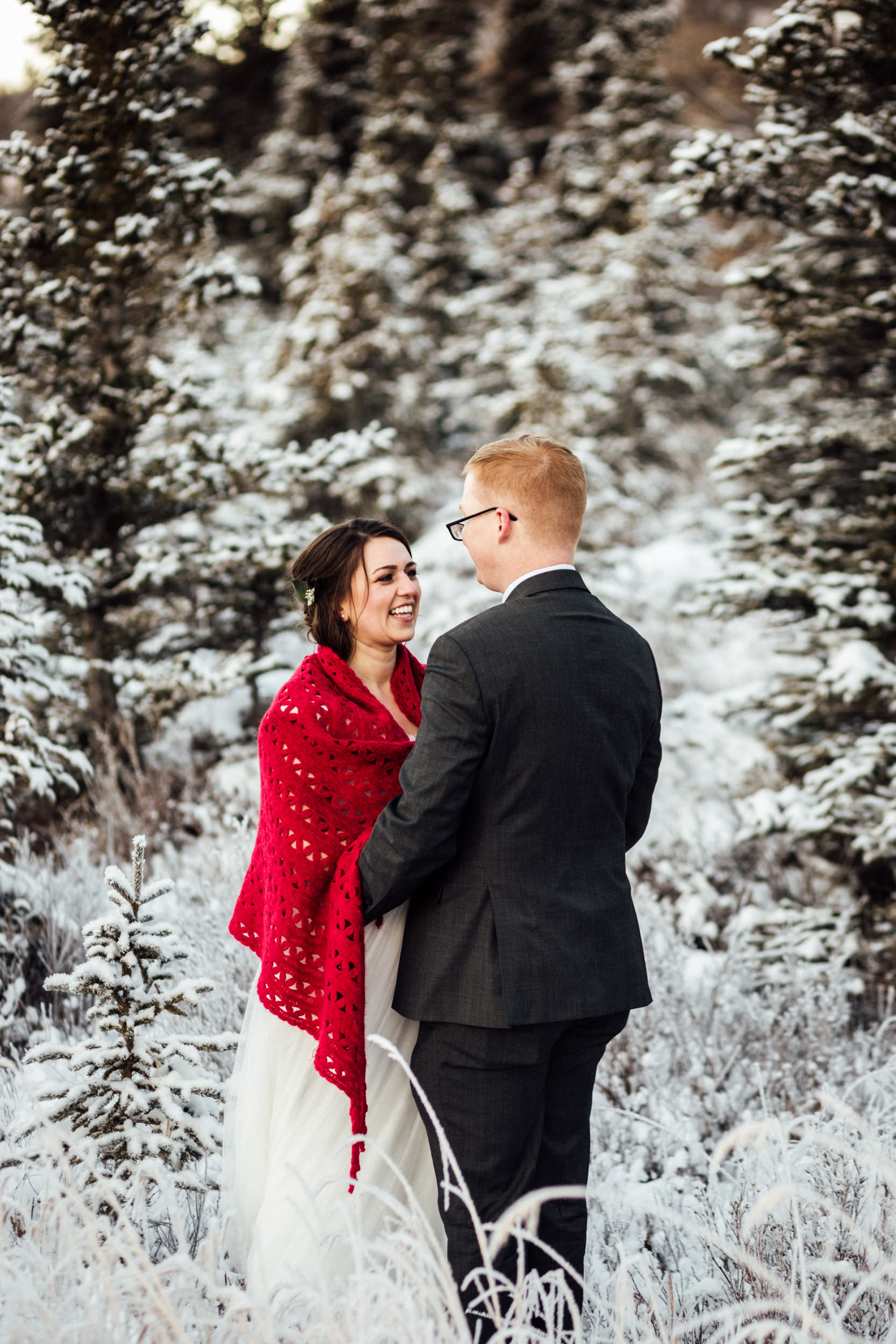 Couple smiling at one another among snowy trees