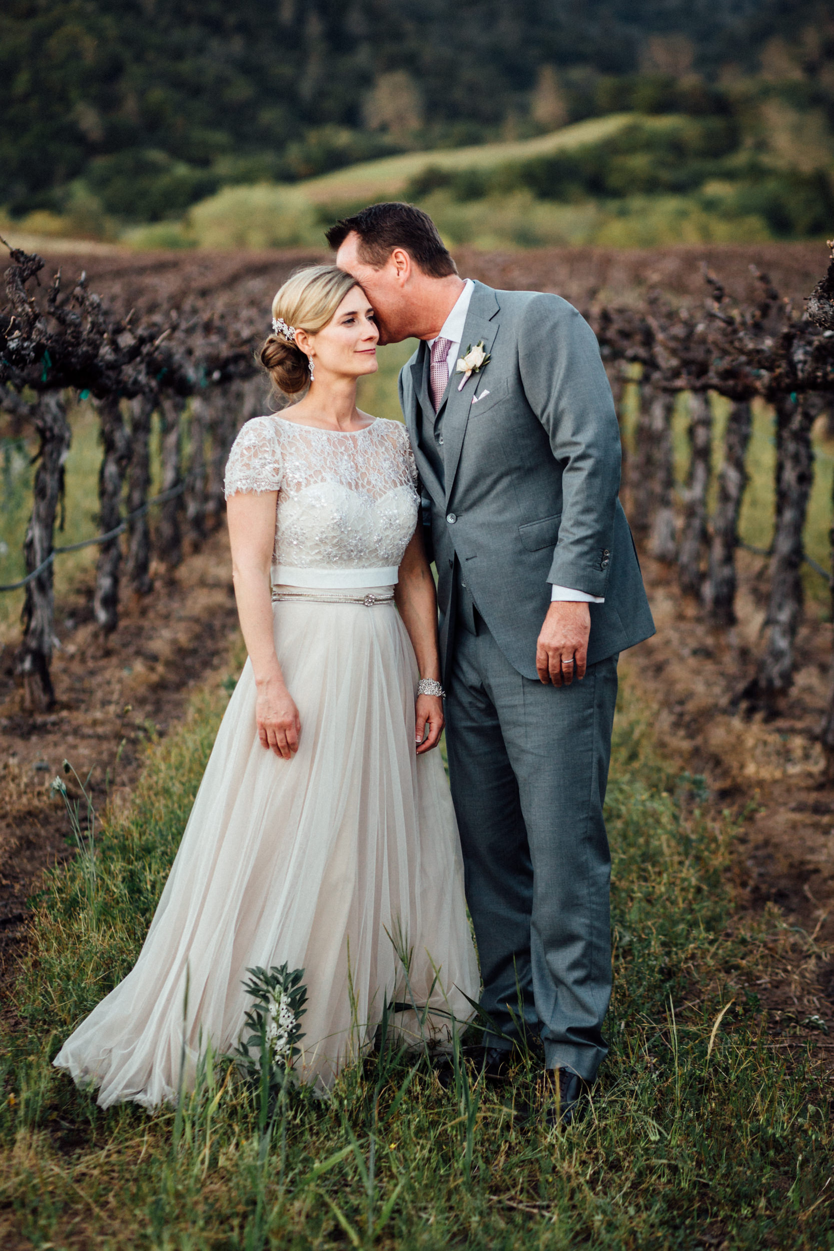 Groom whispering to bride in vineyard