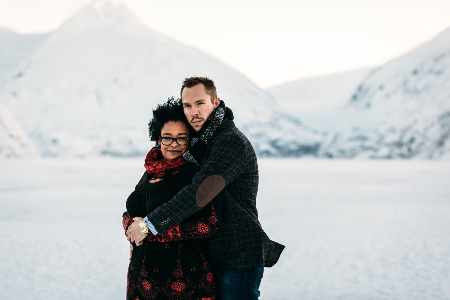 couple hugging during engagement photos in alaska