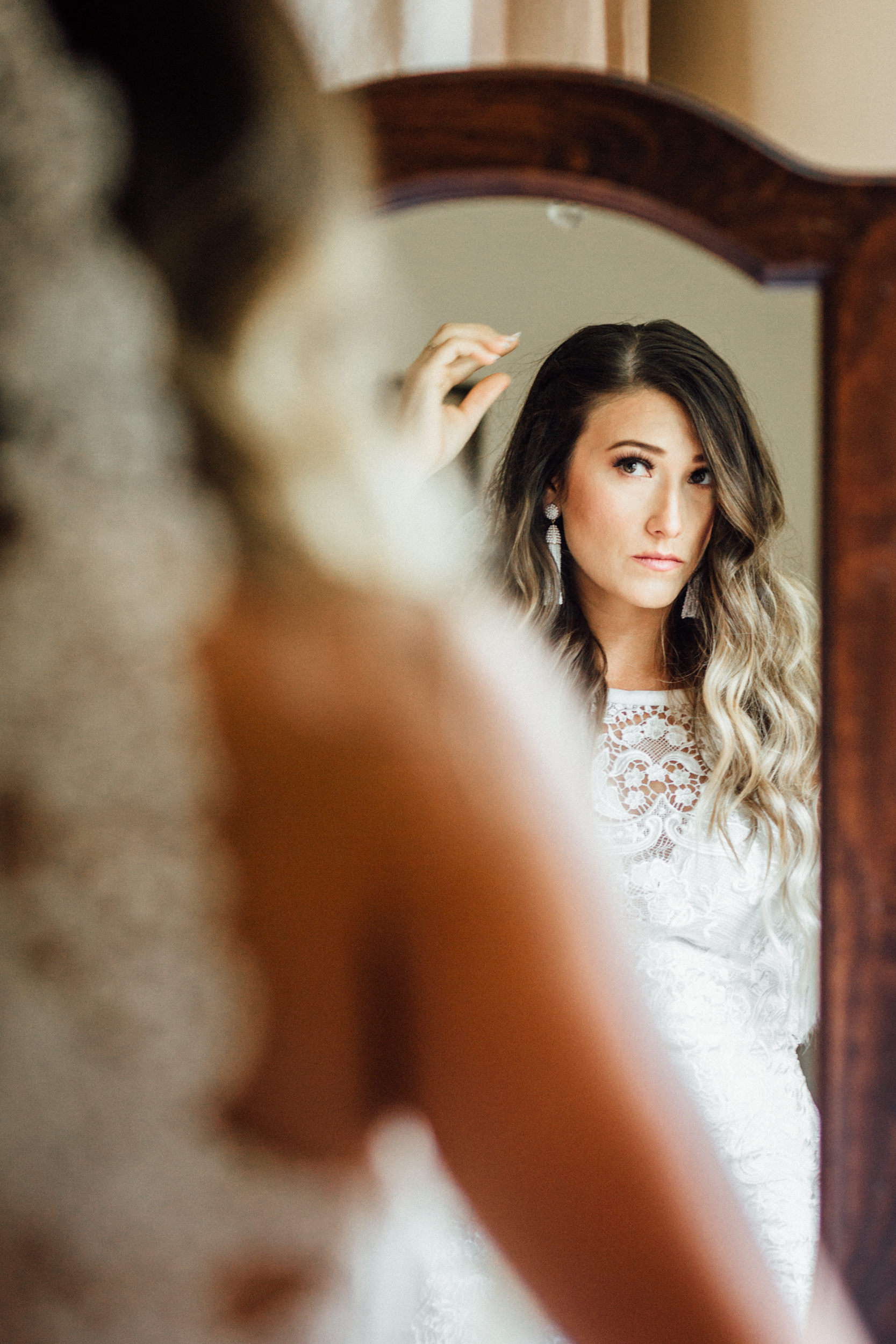 Bride looking in mirror and fixing hair