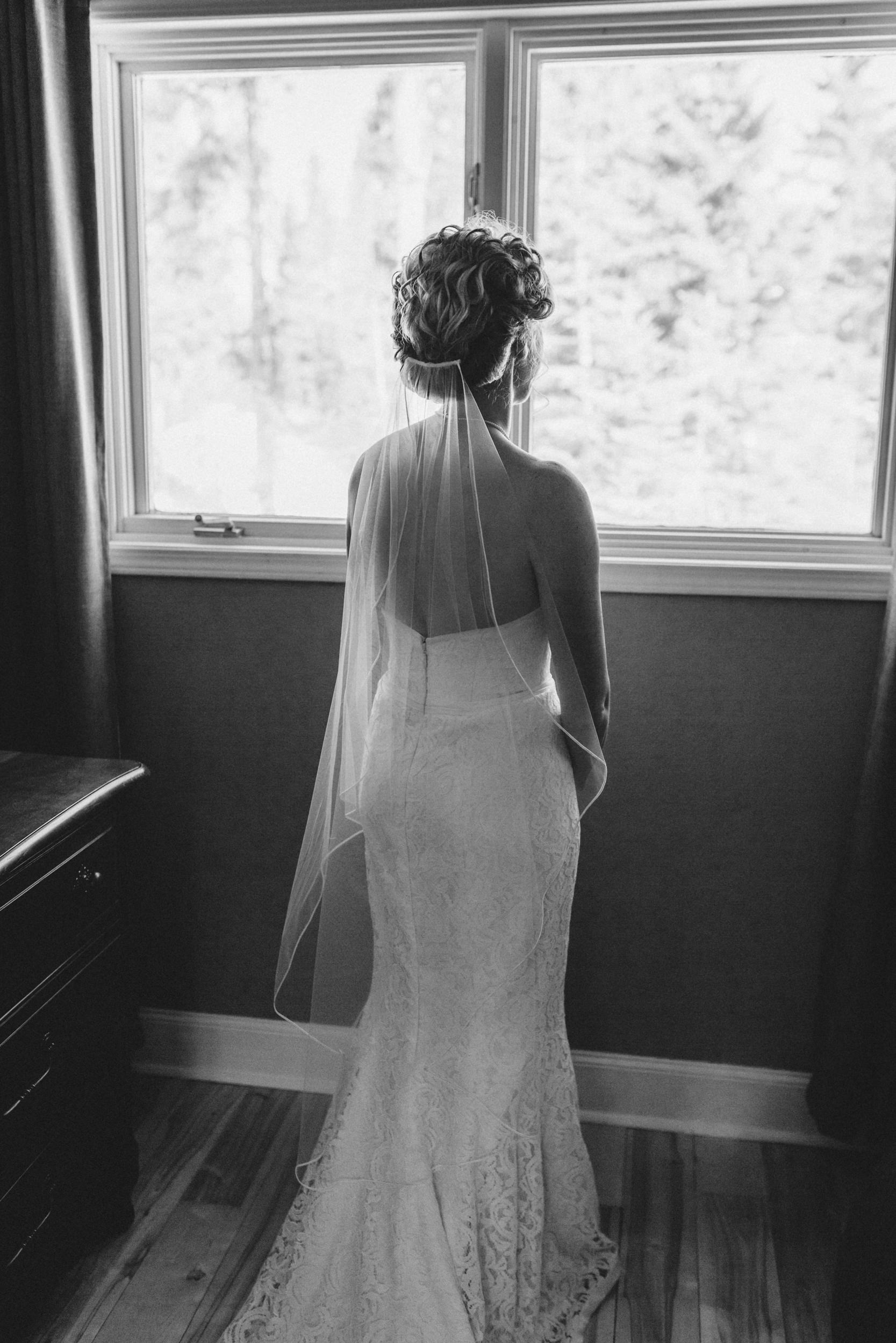 Portrait of bride looking out the window