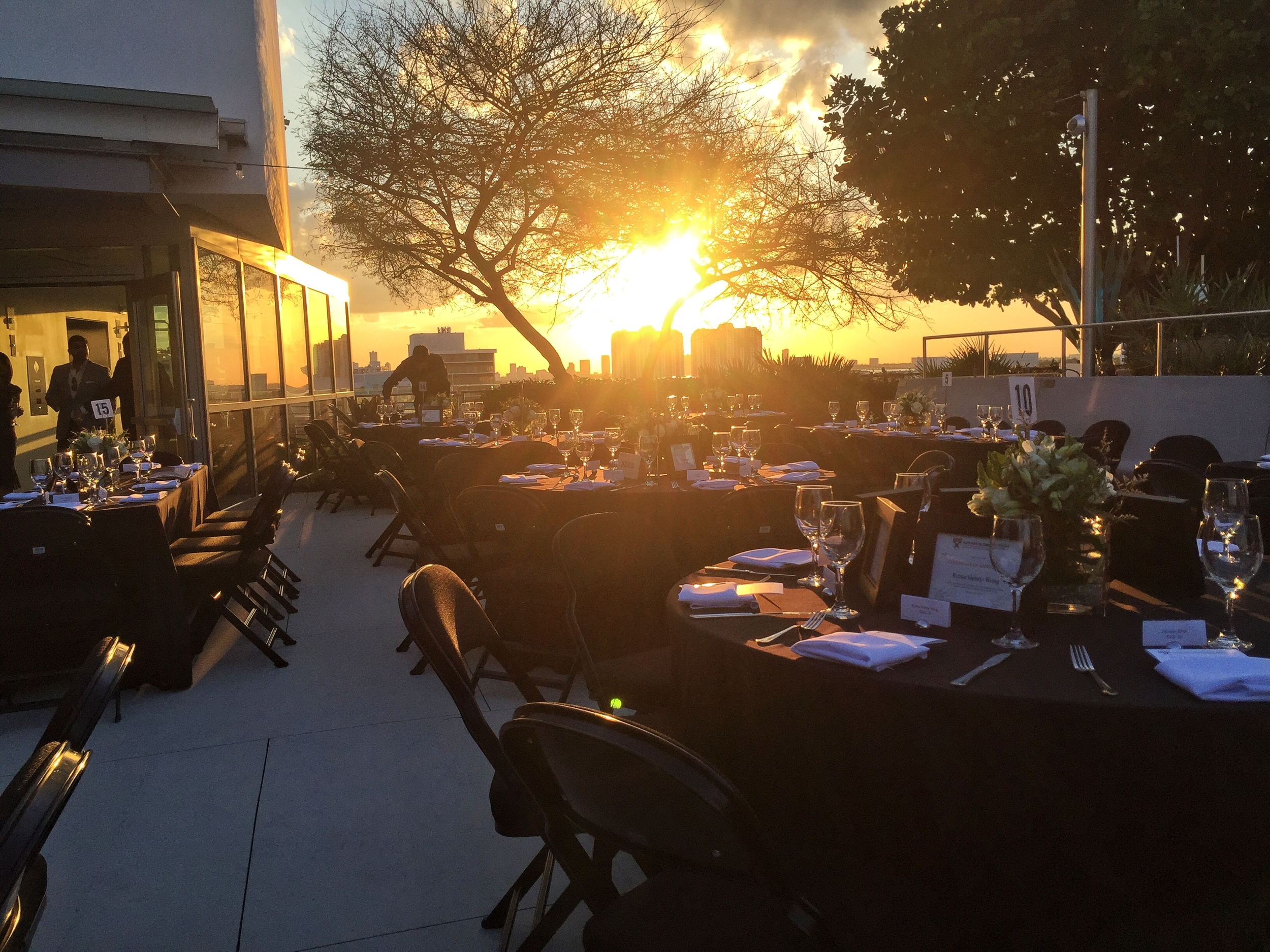 Tables set at golden hour for a beautiful dinner on the New World Center rooftop