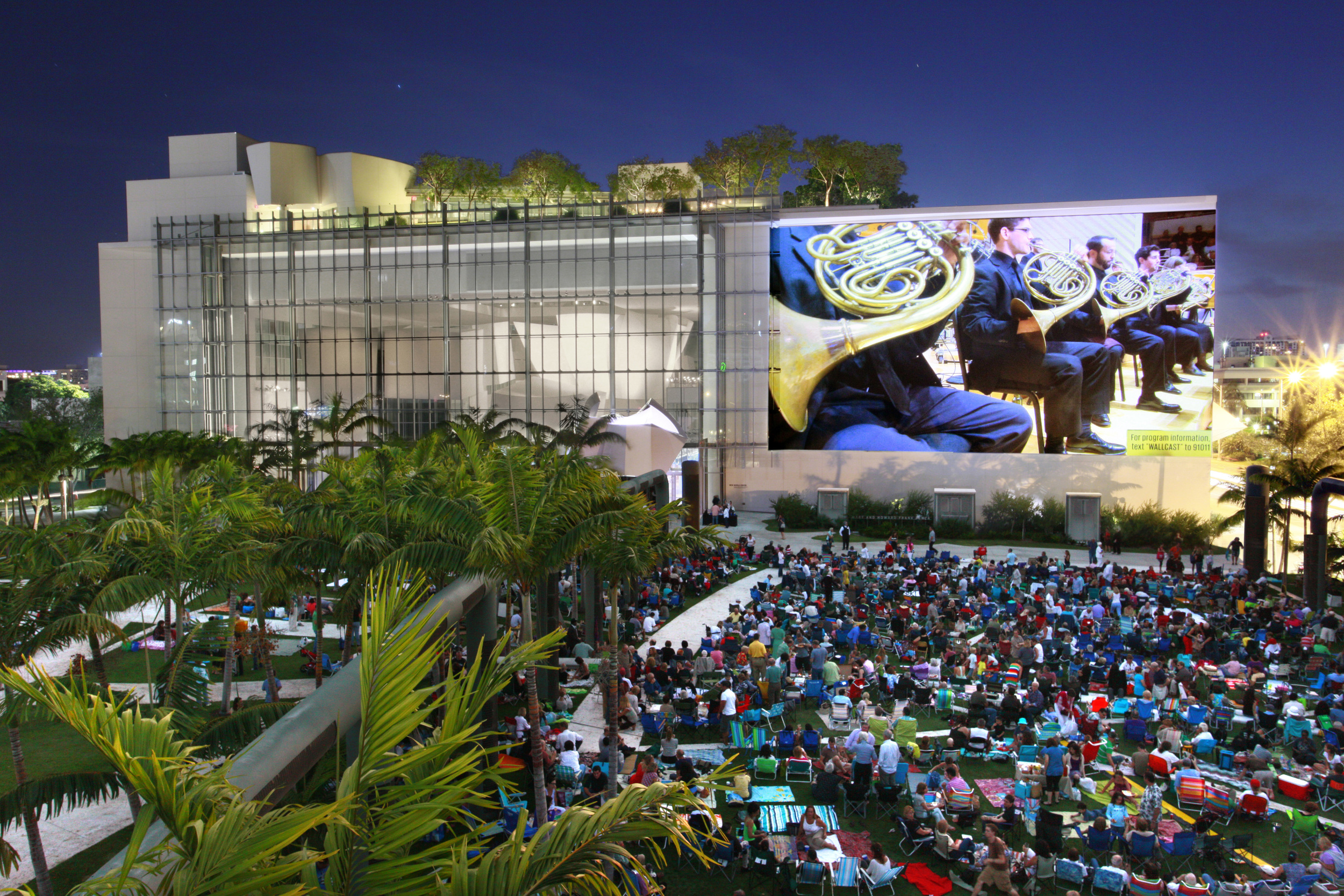 The New World Symphony WALLCAST events are free to the public and allow the community to enjoy select events from the lawns of SoundScape park, on the vast 7000 square foot projection wall, all thanks to a stunning use of high audio and visual technology. (Photo courtesy of New World Center.)