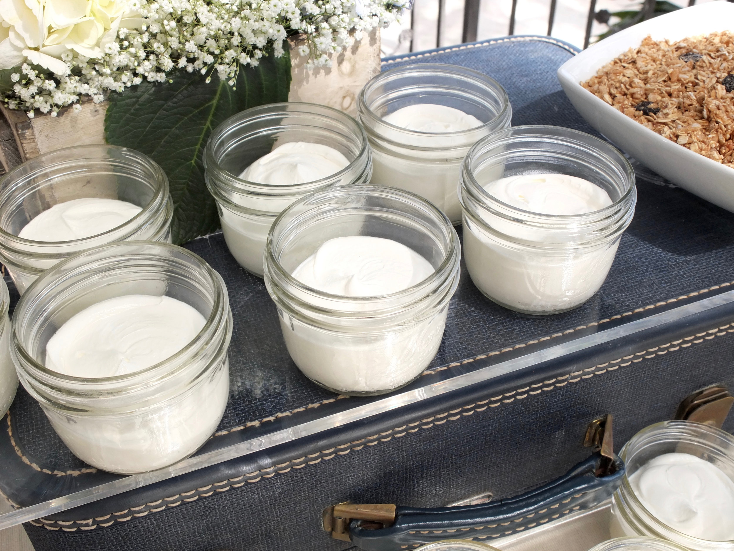 Mason Jar Yogurt Parfaits with Sides of Granola and Seasonal Fresh Fruit were displayed on antique luggage from Unearthed Vintage's collection.