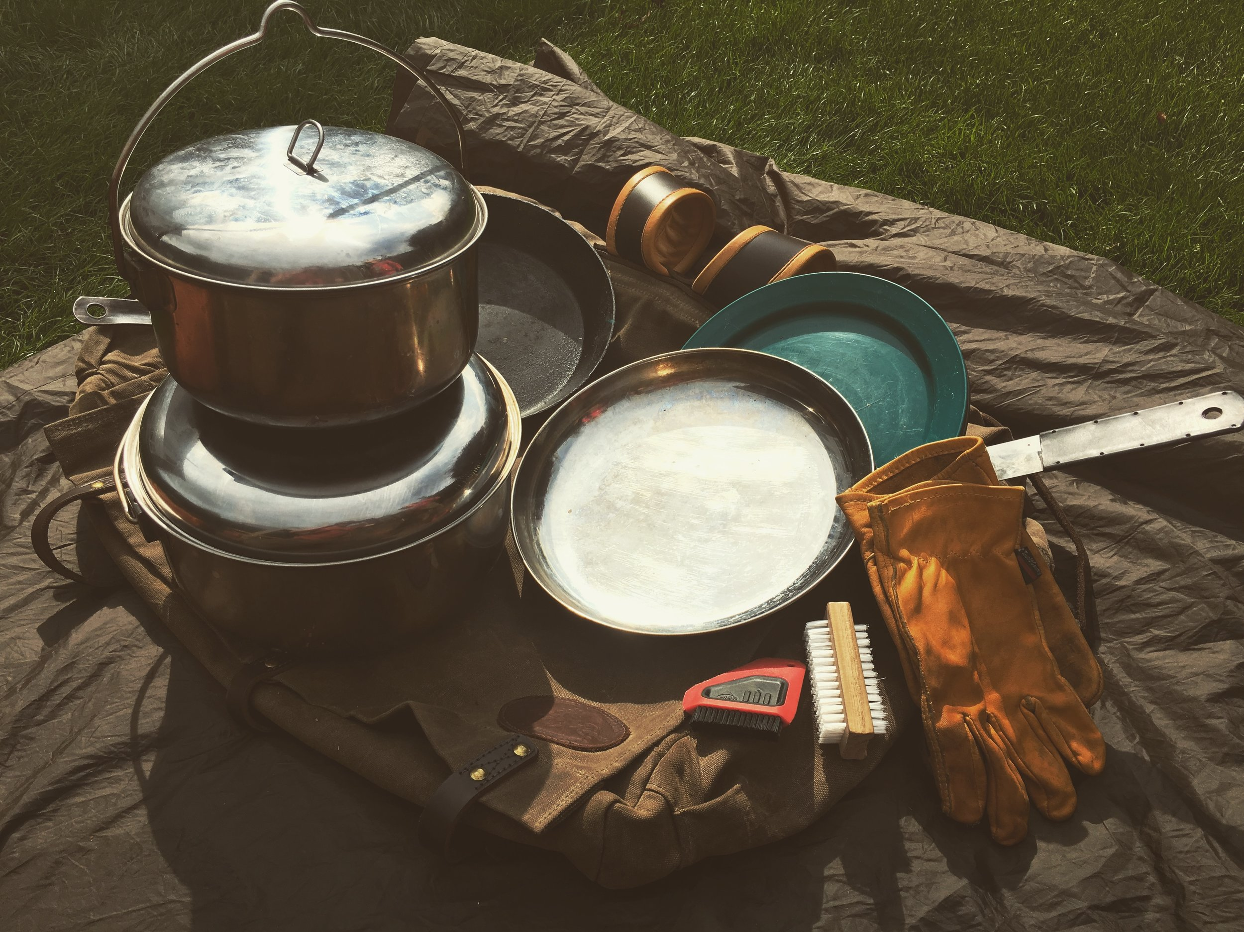 For four people we'll use a couple of stainless steel pots, and a stainless frying pan with collapsible handle. Plastic plates double as chopping boards. I find a nail brush is an excellent tool for scrubbed pans when cleaning on the trail. Leather gloves are also useful when cooking by the fire.