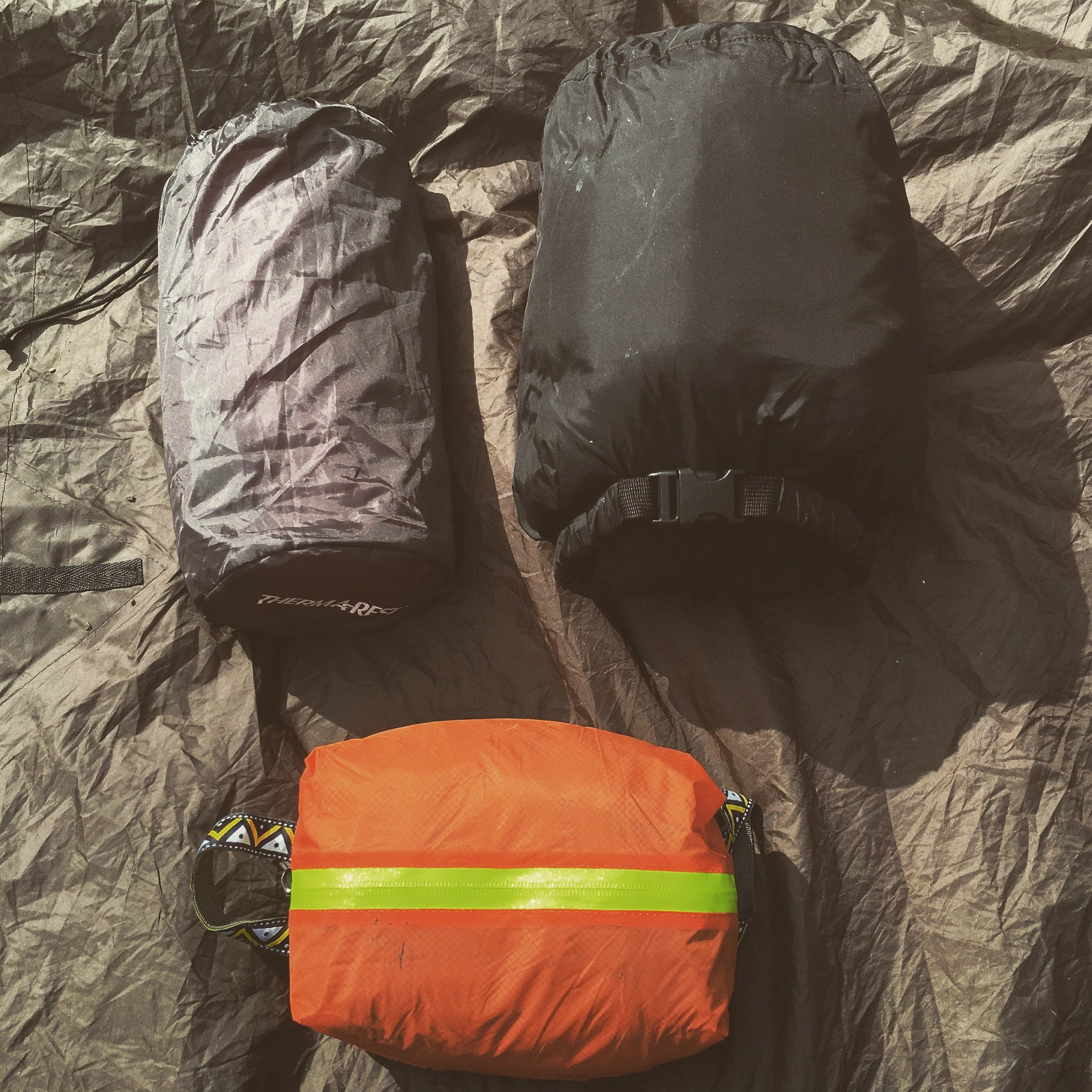 Bed Bag: This dedicated dry bag stows my sleeping gear. I carry a Mountain Equipment Down winter down bag from October, inside its own dry bag (that's three dry bags deep into my kit, within the Timber Cruiser!) It packs small and light, and being down responds better if it's a little warmer than expected. My mat is a Thermarest Prolite 3/4 length mat, very durable and compact it blows up nice and thick for a warm comfy nights sleep. I carry a puncture inside it stuff sack for accidents. The orange bag contains my sleeping clothes, as Mors Kochanski is often quoted: pile lots under you, lots over you and little on you. It's sound advice indeed, as insulation comes from trapped dry air, allow your sleeping bag and mat to do their job. On my person I always strip away my day clothes as any sweat or damp from the outside never wants to wind up in your sleep system. In the bag I have a light merino top, wool hat and buff, and thin wool gloves as well as wool socks. These are all I sleep in even when it's very cold, if I get colder still I'll pull my Keela jacket from my ditch kit  over  my sleeping bag to help trap more air. Further into winter I may include a pair of thermal leggings as well.