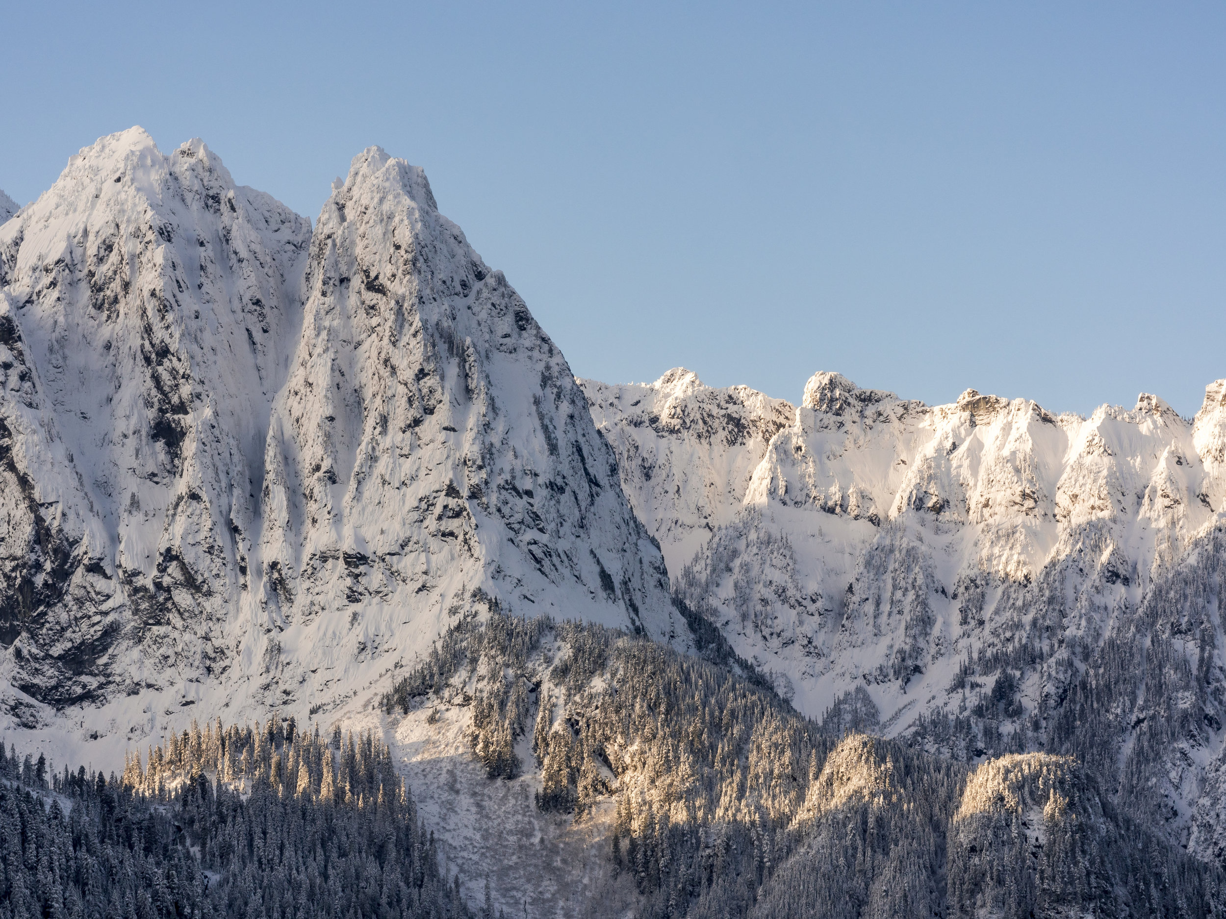 Snow Covered Jagged Peaks with Blue Sky Background in North Cascade Mountain Range