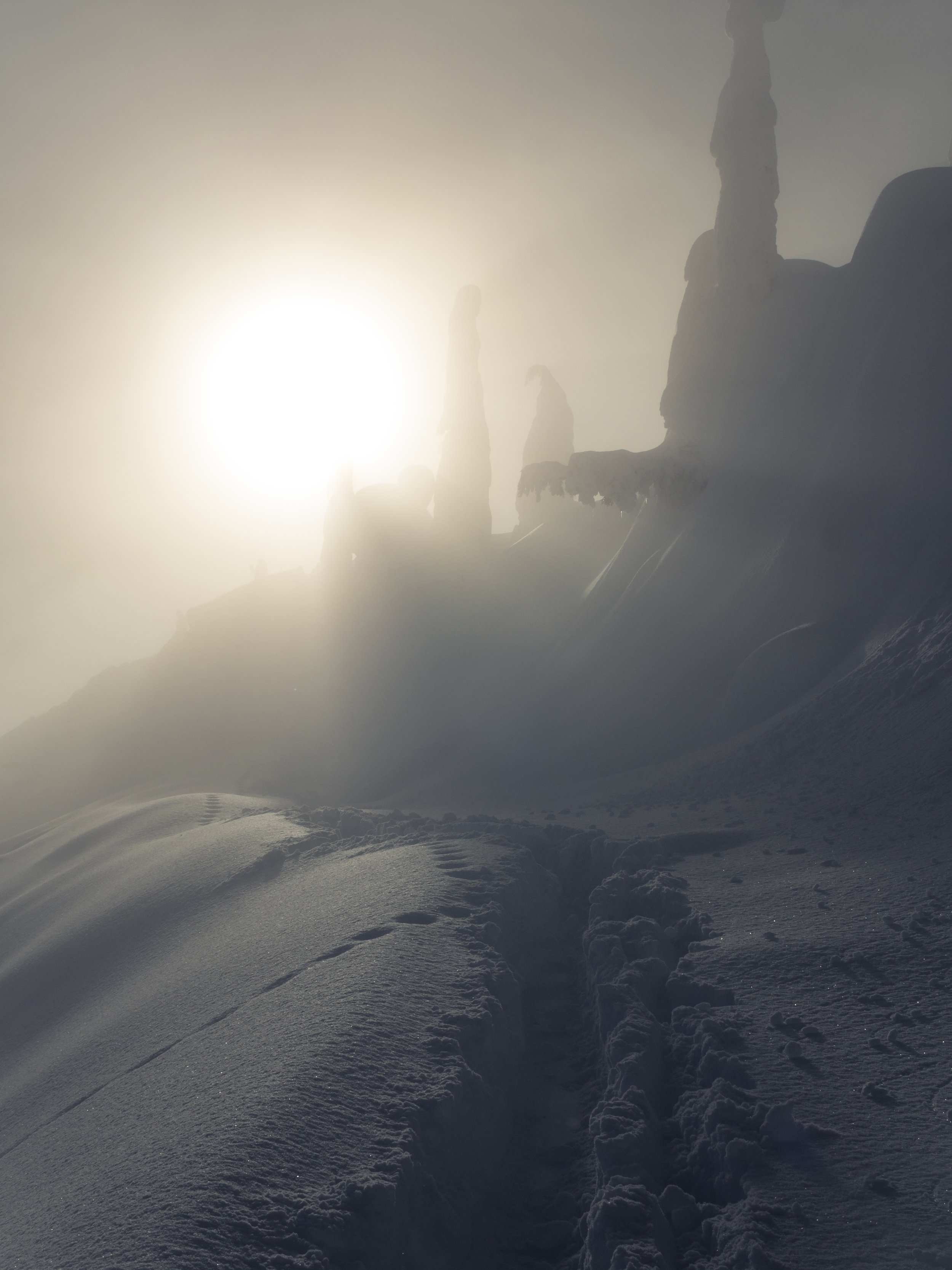Boot Pack Hiking Trail in Deep Powder Snow with Sun Rays in Hazy Fog Cloud