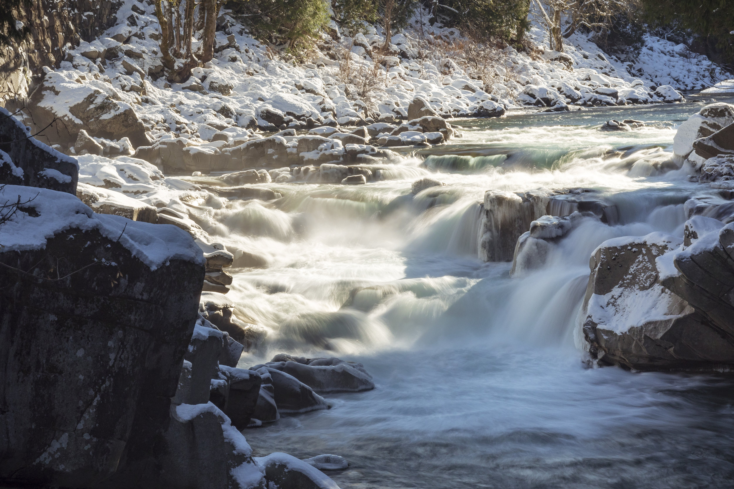 Peaceful_River_Landscape_Flowing_with_White_Water_Rapids_on_Winter_Snow_Covered_Rocks.jpg