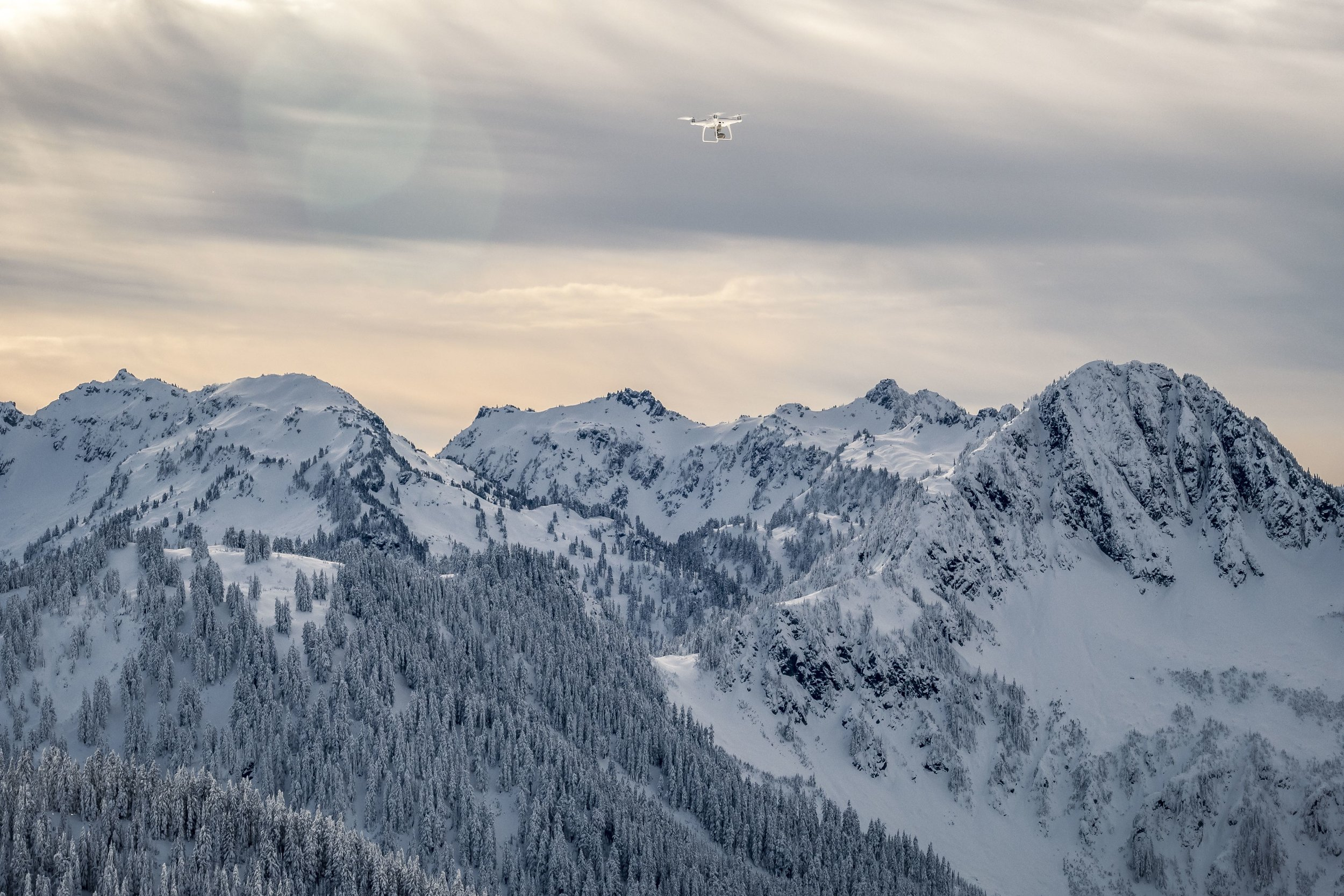 Drone_Flying_Over_Snowy_Mountain_Conditions_in_Winter_Season.jpg